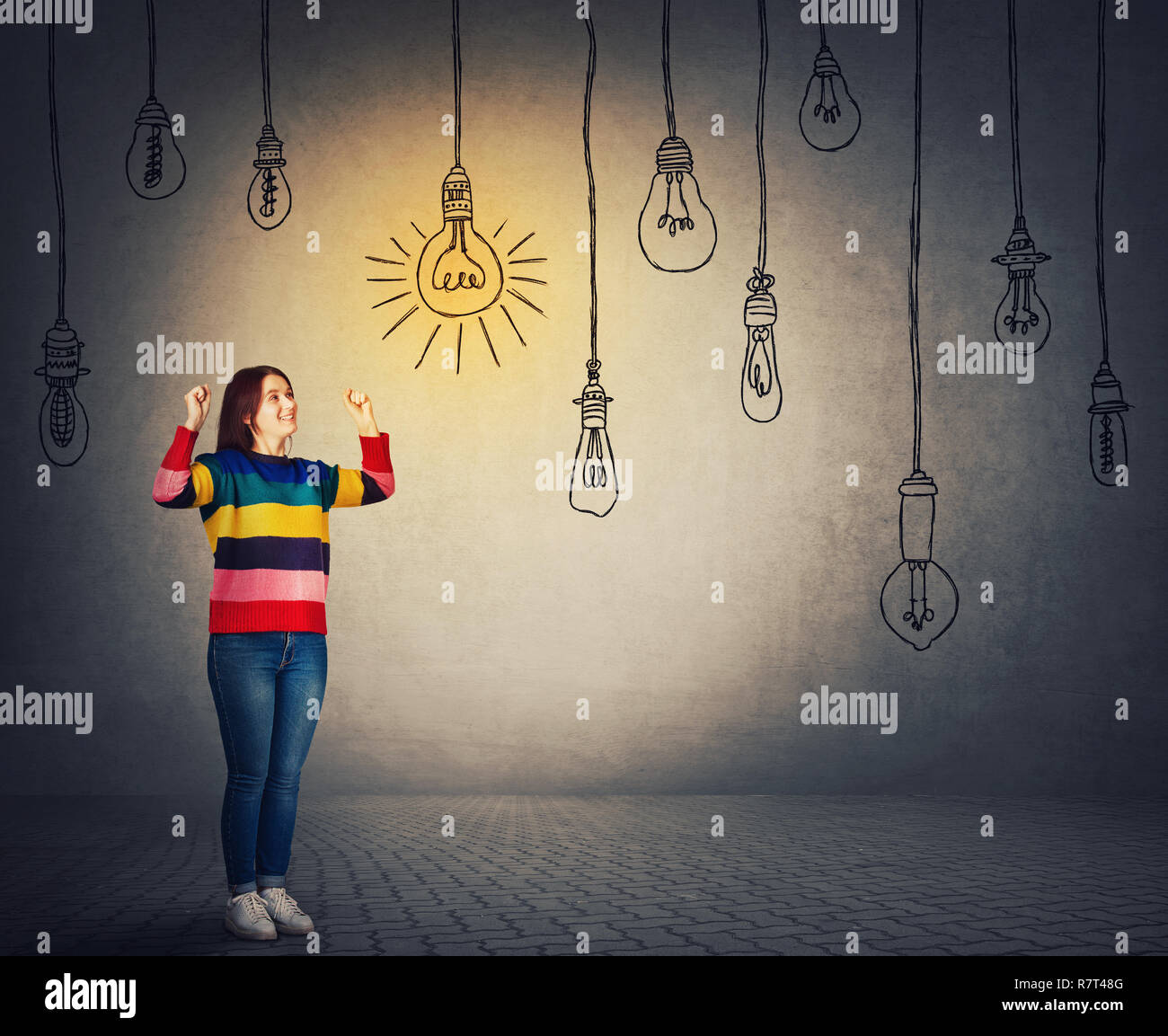 Full length portrait of cheerful young woman celebrate raising fists up looking at a glowing, suspended lightbulb. One bulb shine while others are swi - Stock Image