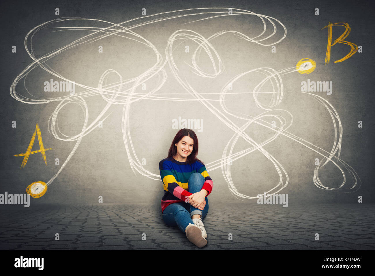 Pretty casual woman sitting on the floor finding the correct way from point A to point B. Solving problem, find solution, business idea and creativity - Stock Image