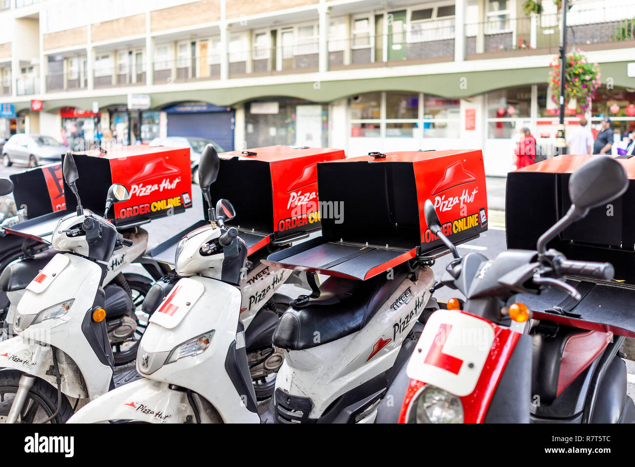 London, UK - September 16, 2018: Row of many Pizza Hut online delivery scooters, motorcycles parking, parked by road street curb in Pimlico with nobod - Stock Image
