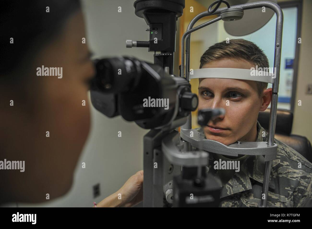 U.S. Air Force Maj. See Vang, 51st Aerospace Medicine Squadron optometry flight commander, left, scans the eye of Staff Sgt. River Carson, 8th Medical Operations Squadron public health technician, using the slit lamp during his eye exam at Kunsan Air Base, Republic of Korea, March 24, 2017. The slit lamp uses an intense beam of light to show the eye in detail to check for abnormalities during eye checkups. - Stock Image