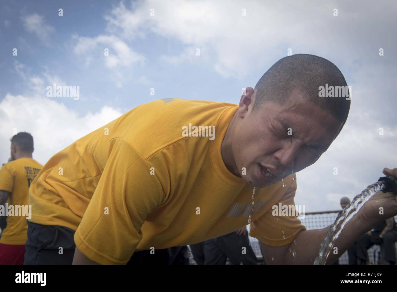 SOUTH CHINA SEA (April 8, 2017)  Culinary Specialist 1st Class Wilson Ebreo, right, decontaminates following exposure to oleoresin capsicum during security reactionary forces training aboard the Arleigh Burke-class guided-missile destroyer USS Stethem (DDG 63). Stethem is on patrol in the South China Sea supporting security and stability in the Indo-Asia-Pacific region. Stock Photo