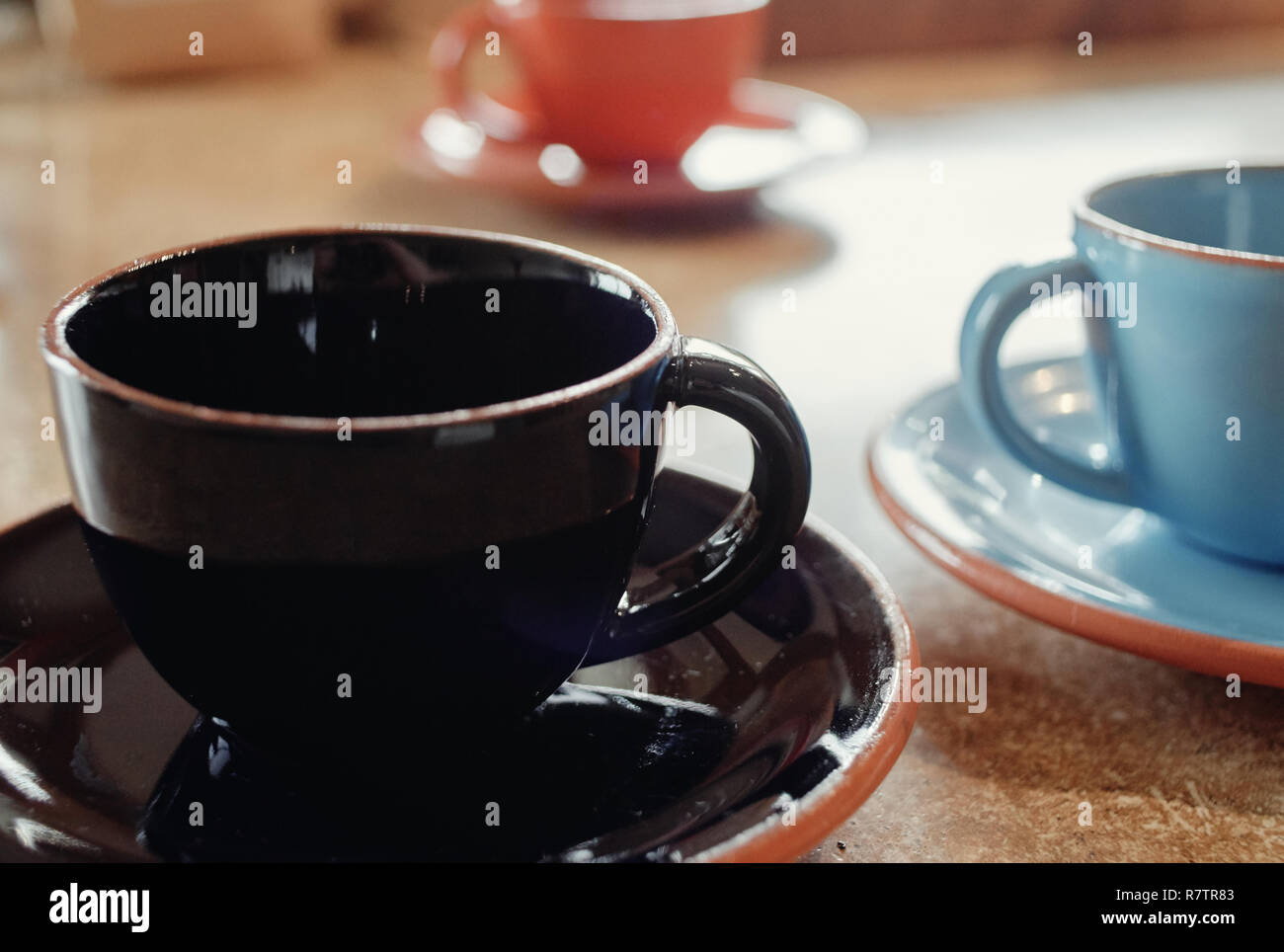 3 coffee cups and saucers brightly lit on table - Stock Image