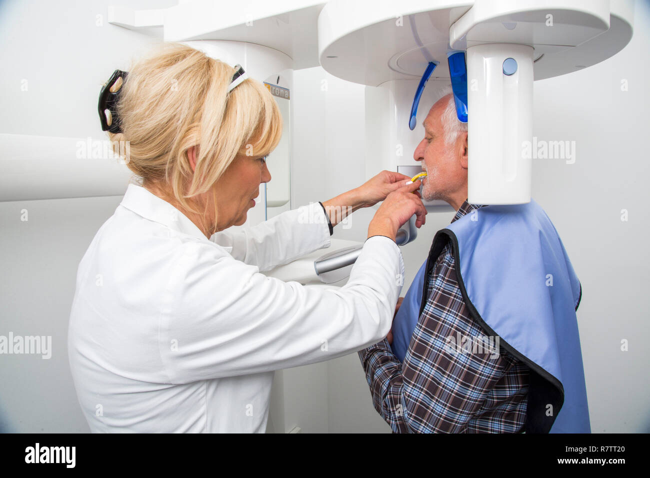 Man being prepared for an X-ray of his teeth, wearing a lead vest for protection from radiation, Germany - Stock Image