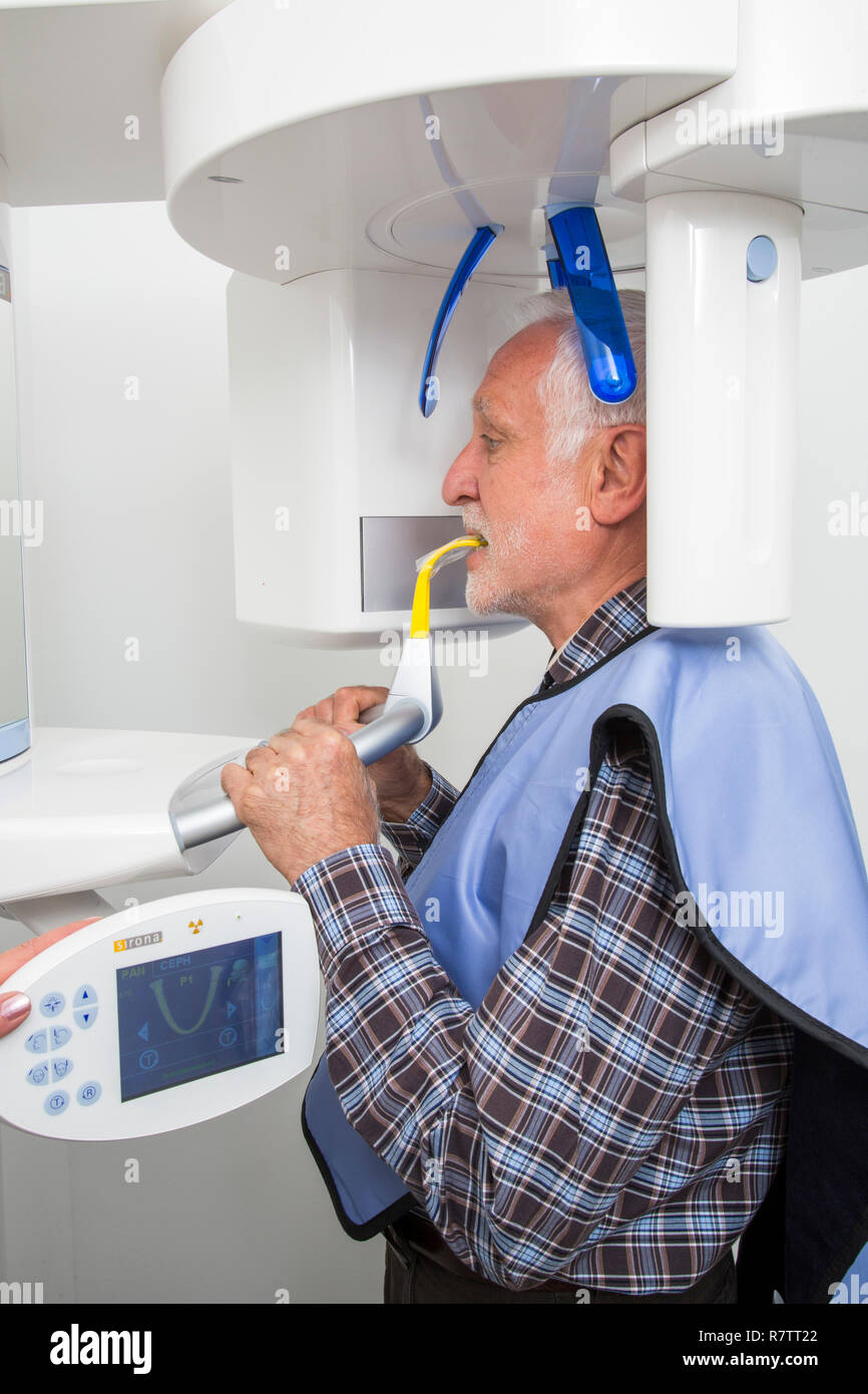 Man receiving an X-ray of his teeth, wearing a lead vest for protection from radiation, Germany - Stock Image