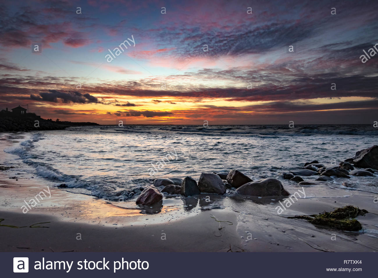 Dramatic sunset over ocean with stones in foreground - Stock Image