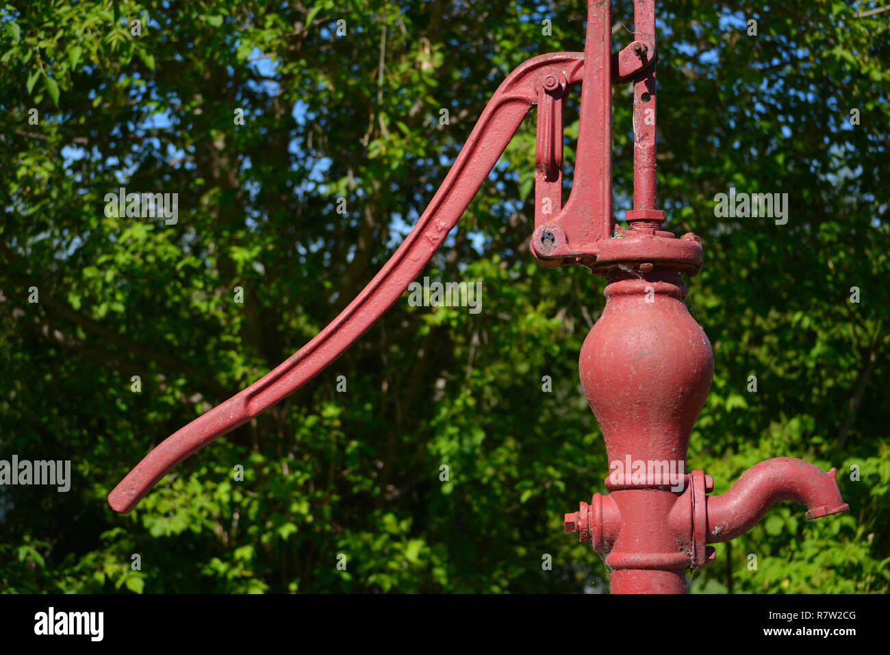 Hand water pump with farm yard shelter trees - Stock Image