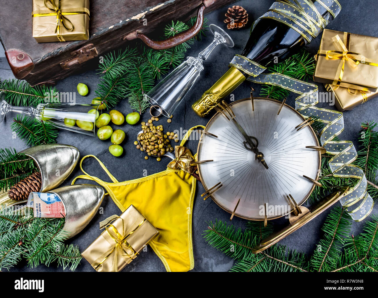 LATIN AMERICAN AND SPANISH NEW YEAR TRADITIONS. empty suitcase, lentil spoon, yellow interior clothes, gold ring in champagne, 12 grapes, money in sho - Stock Image
