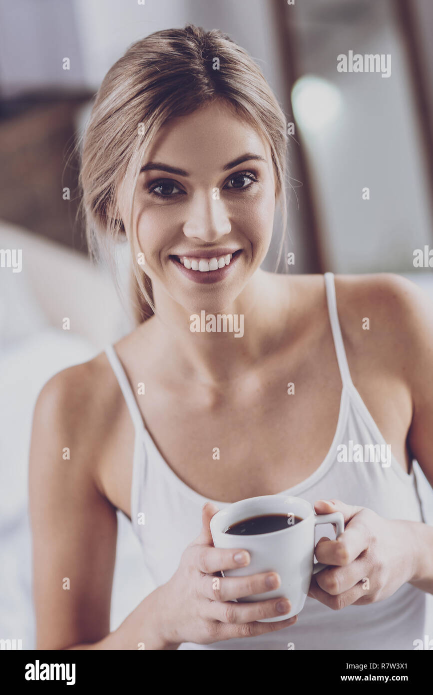 Blonde woman drinking coffee at home - Stock Image