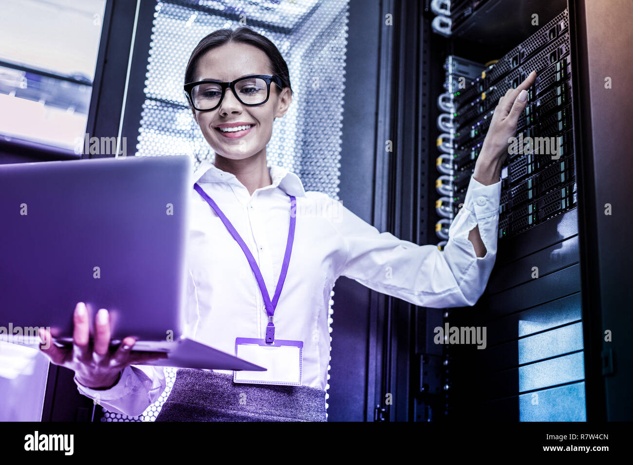 Cheerful nice woman looking at the laptop screen - Stock Image