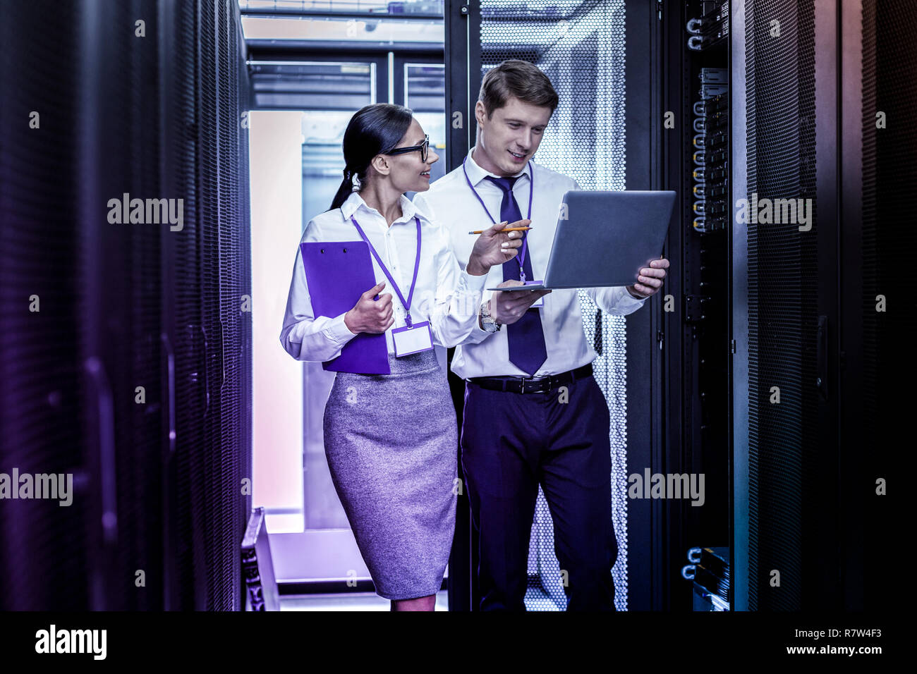 Cheerful positive woman discussing work with her colleague - Stock Image