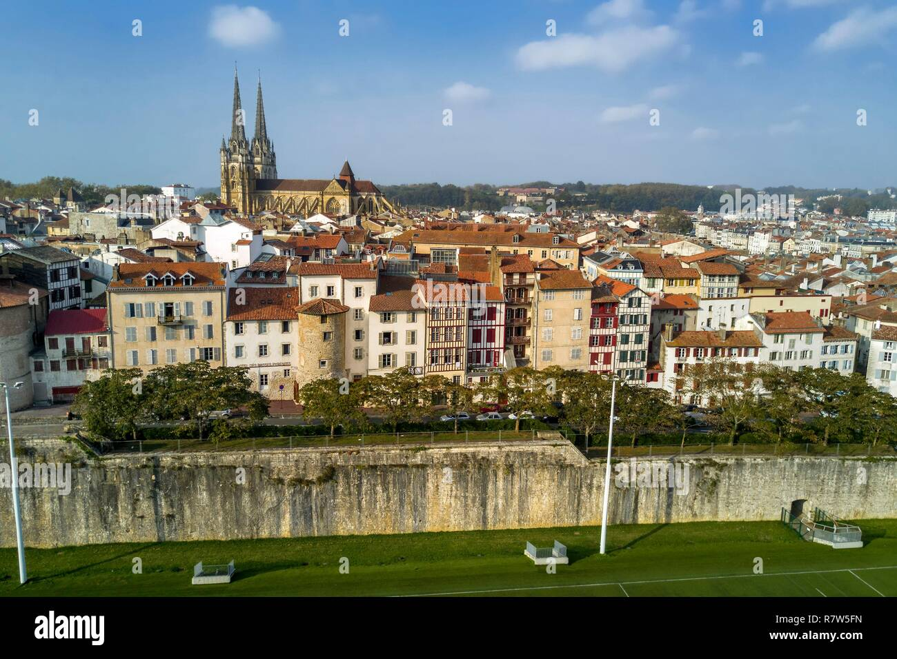 France, Pyrenees Atlantiques, Basque Country, Bayonne, the spires of St. Catherine's Cathedral behind the towers of the former ramparts integrated in the buildings of the rue Tour de Sault, the fortifications of Vauban in the foreground (aerial view) - Stock Image