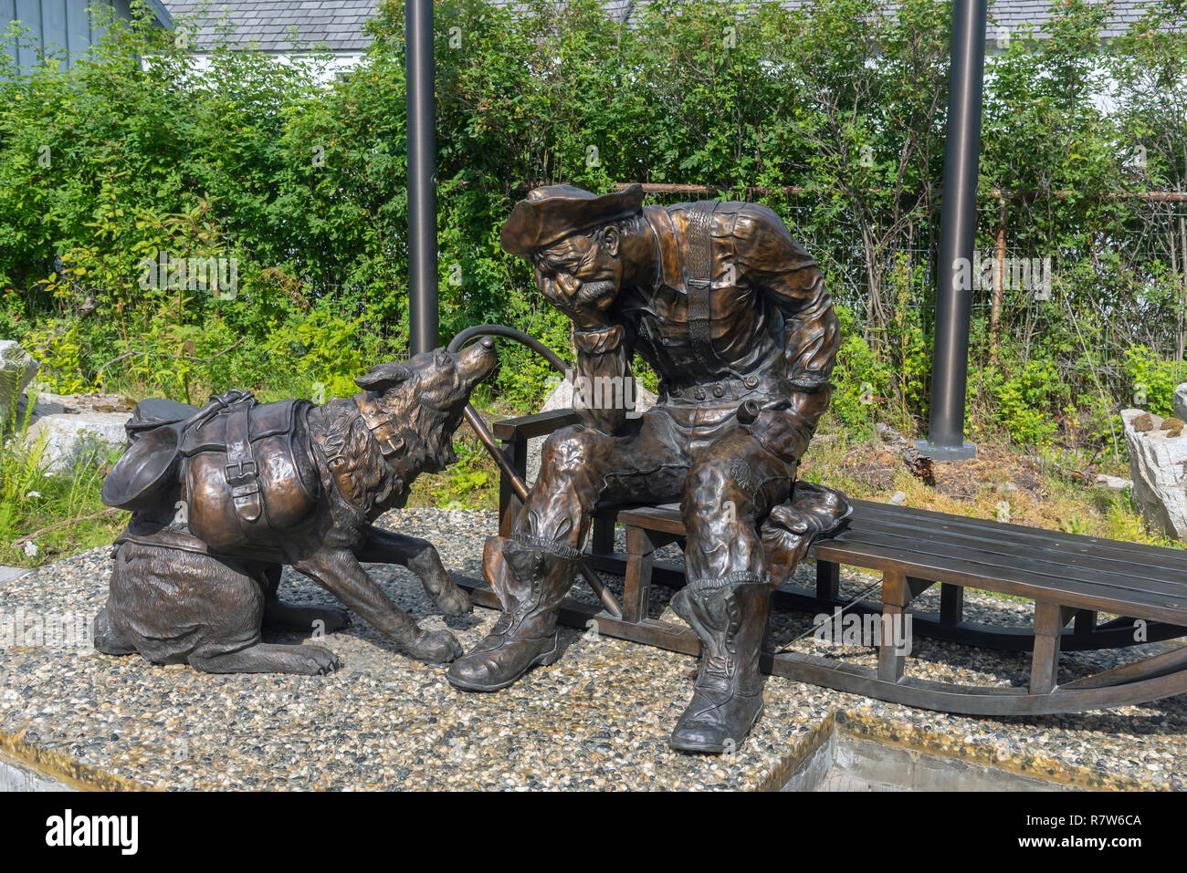 A sculpture of a prospector and his dog near the Alaska Geographic Museum Store, Skagway, Alaska, Klondike Gold Rush National Historical Park, USA - Stock Image