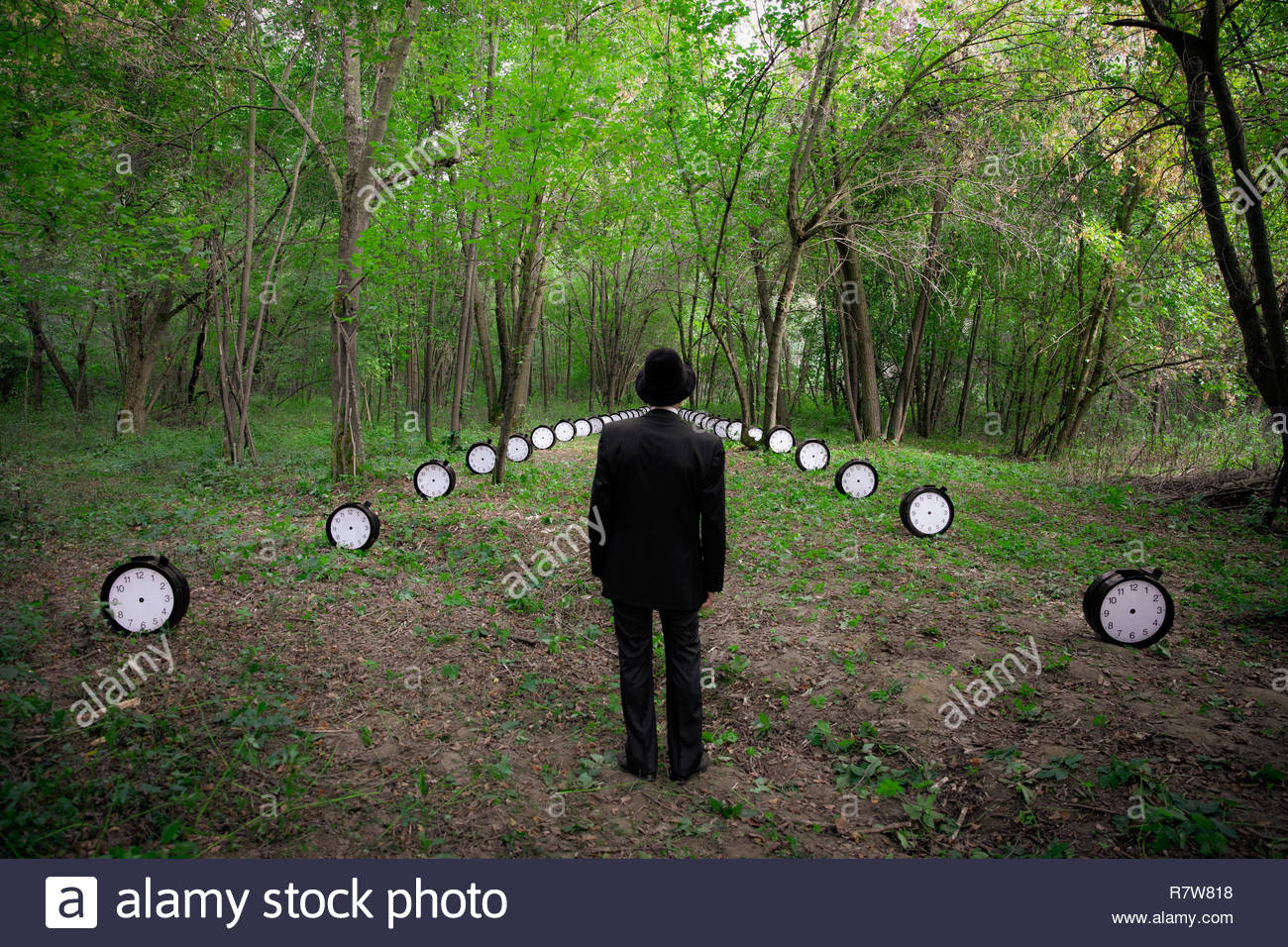 A man dressed in black, within a forest, stands in the foreground, at the beginning of a time path made by 50 no-hand clocks. - Stock Image