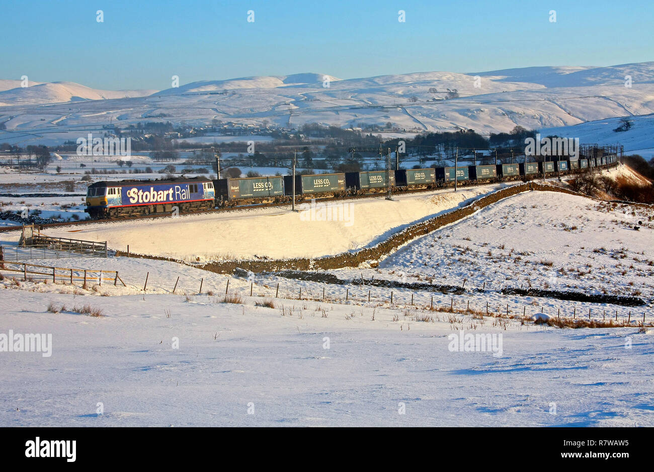 92017 passes Greenholme with the Tesco Express. - Stock Image