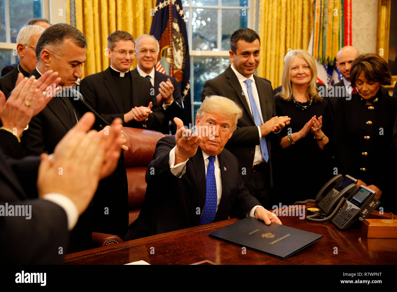 """Washington, United States Of America. 11th Dec, 2018. United States President Donald J. Trump signs H.R. 390, the """"Iraq and Syria Genocide Relief and Accountability Act of 2018"""" in the Oval Office of the White House, in Washington, DC, December 11, 2018. Credit: Martin H. Simon/CNP 