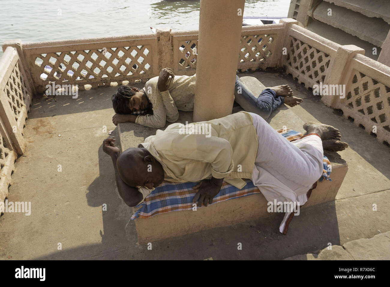 July 23, 2018 - Varanasi, Uttar Pradesh, India - Men are seen resting on the banks of the Ganges river in Varanasi..Varanasi is a city in the northern Indian state of Uttar Pradesh dating to the 11th century B.C. Regarded as the spiritual capital of India, the city draws Hindu pilgrims who bathe in the Ganges River's sacred waters and perform funeral rites. The river is dedicated to the Hindu god Shiva. (Credit Image: © Enzo Tomasiello/SOPA Images via ZUMA Wire) Stock Photo