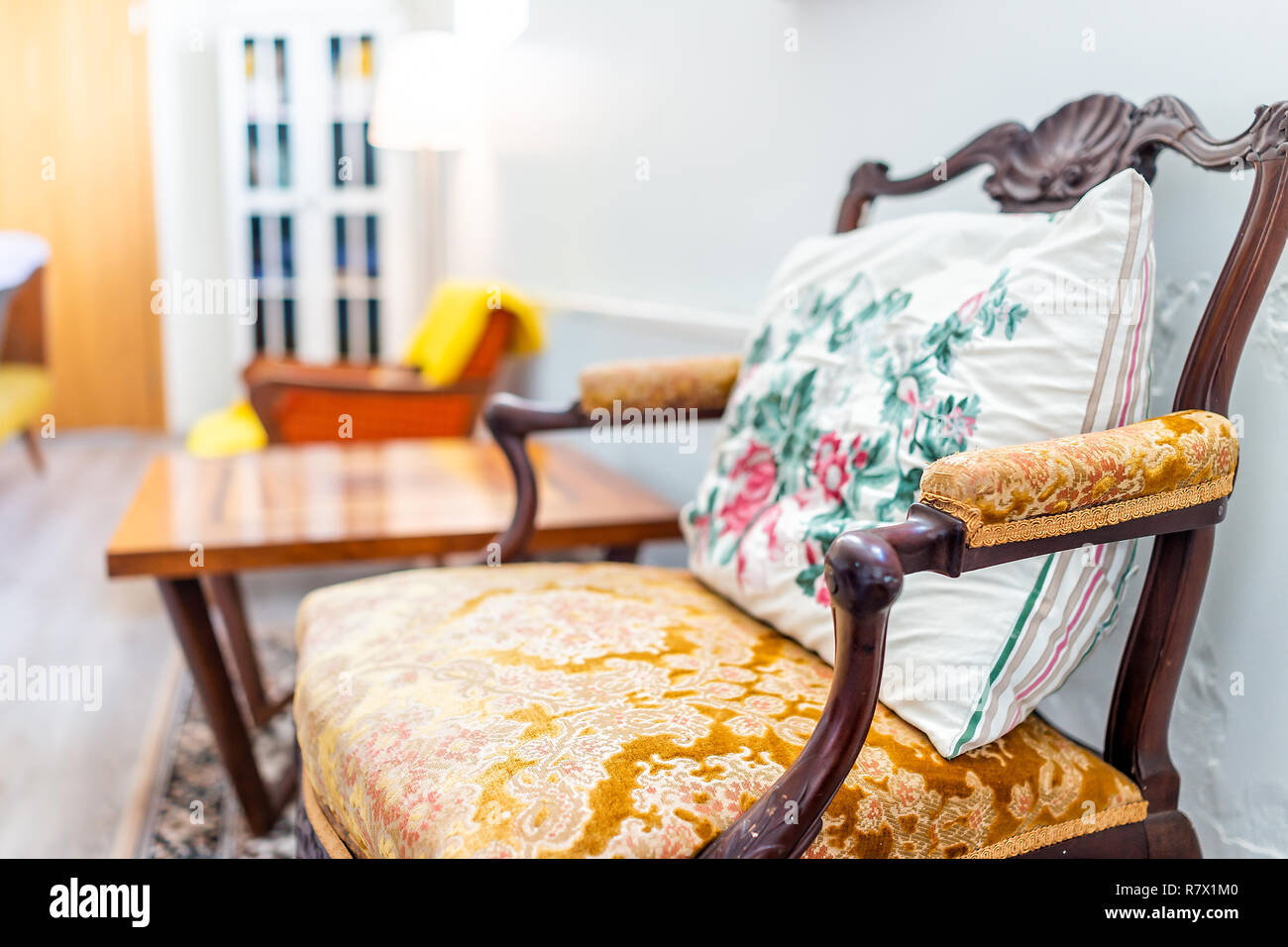 One cozy comfortable vintage armchair home or house living room, floral pillow, table and door, bright lamp - Stock Image