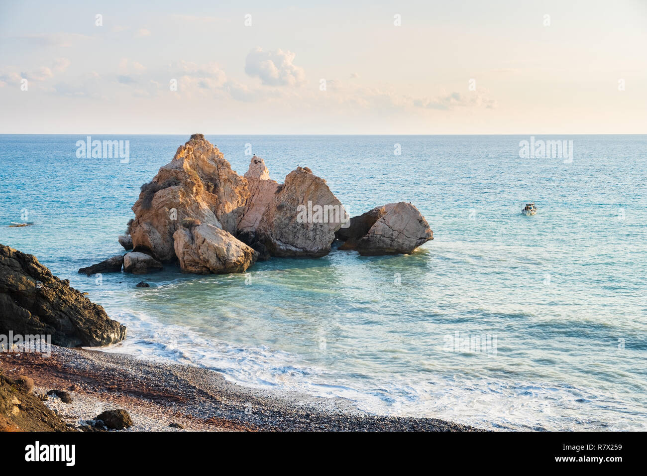 Afternoon view of the seascape around Petra tou Romiou, in Paphos, Cyprus, as a fishing boat passes by. It is considered to be Aphrodite's birthplace  Stock Photo