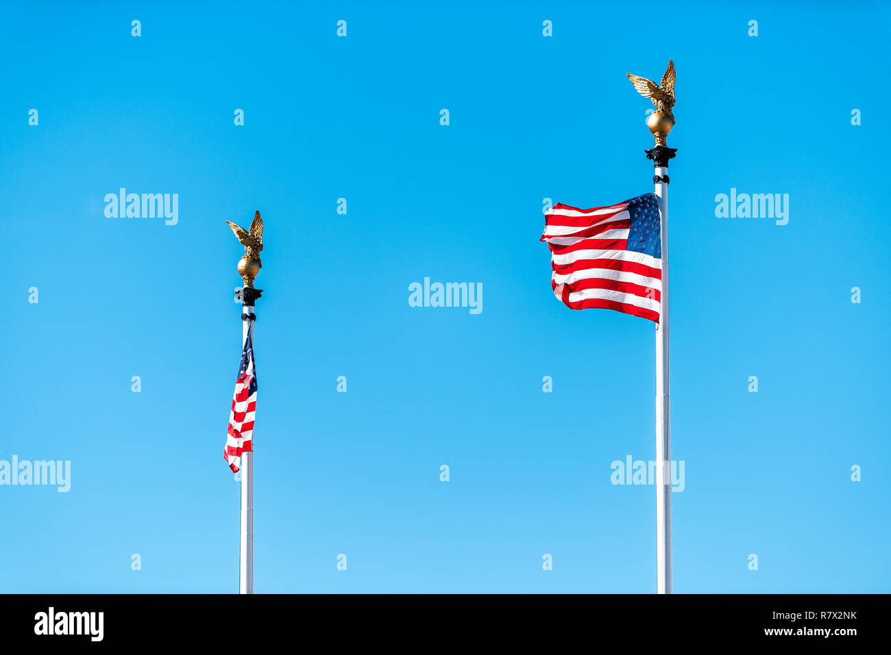 Washington DC, USA Union Station two flagpoles American Flags on poles on street, isolated against colorful color vibrant blue sky closeup - Stock Image