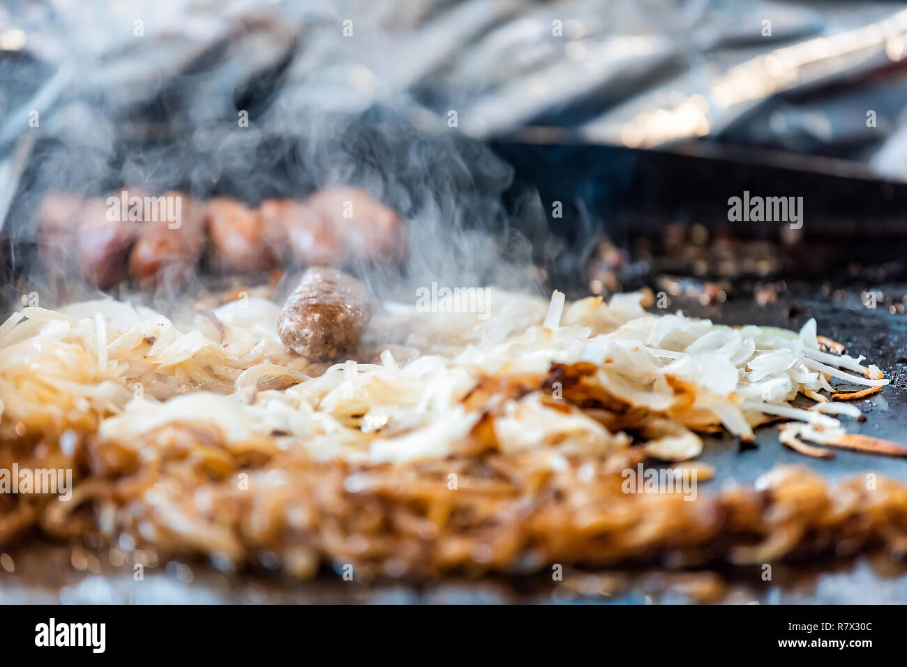 Fast food counter grill with cooking fresh onions, beef pork meat in truck, hot steam closeup, nobody - Stock Image