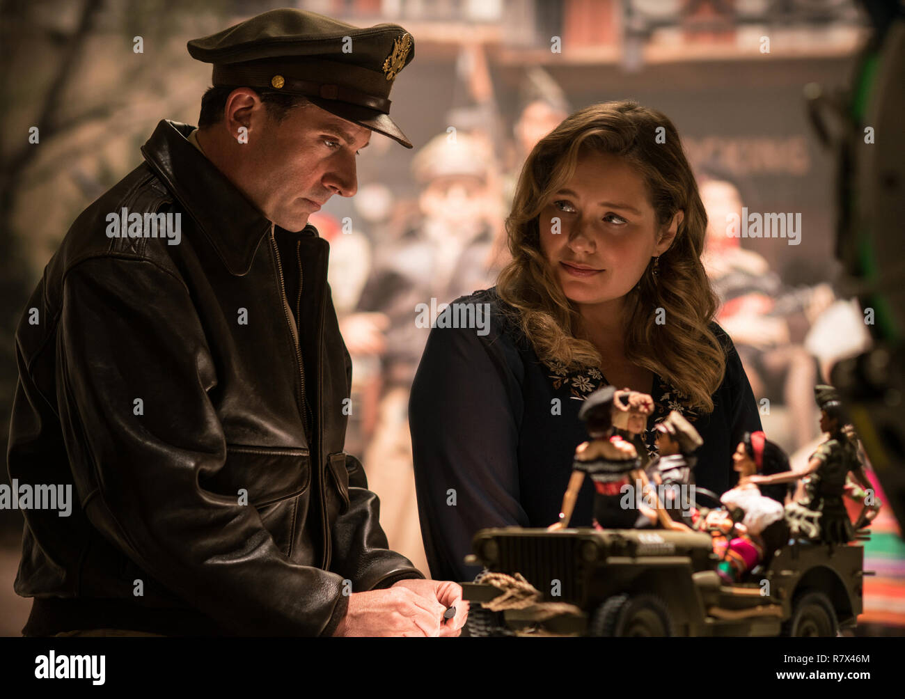 Mark Hogancamp (Steve Carell) and his supportive friend Roberta (Merritt Wever) with the dolls of Mark's fictional town in 'Welcome to Marwen,' directed by Robert Zemeckis.  Photo Credit: Universal Pictures and Storyteller Distribution Co., LLC. / The Hollywood Archive - Stock Image