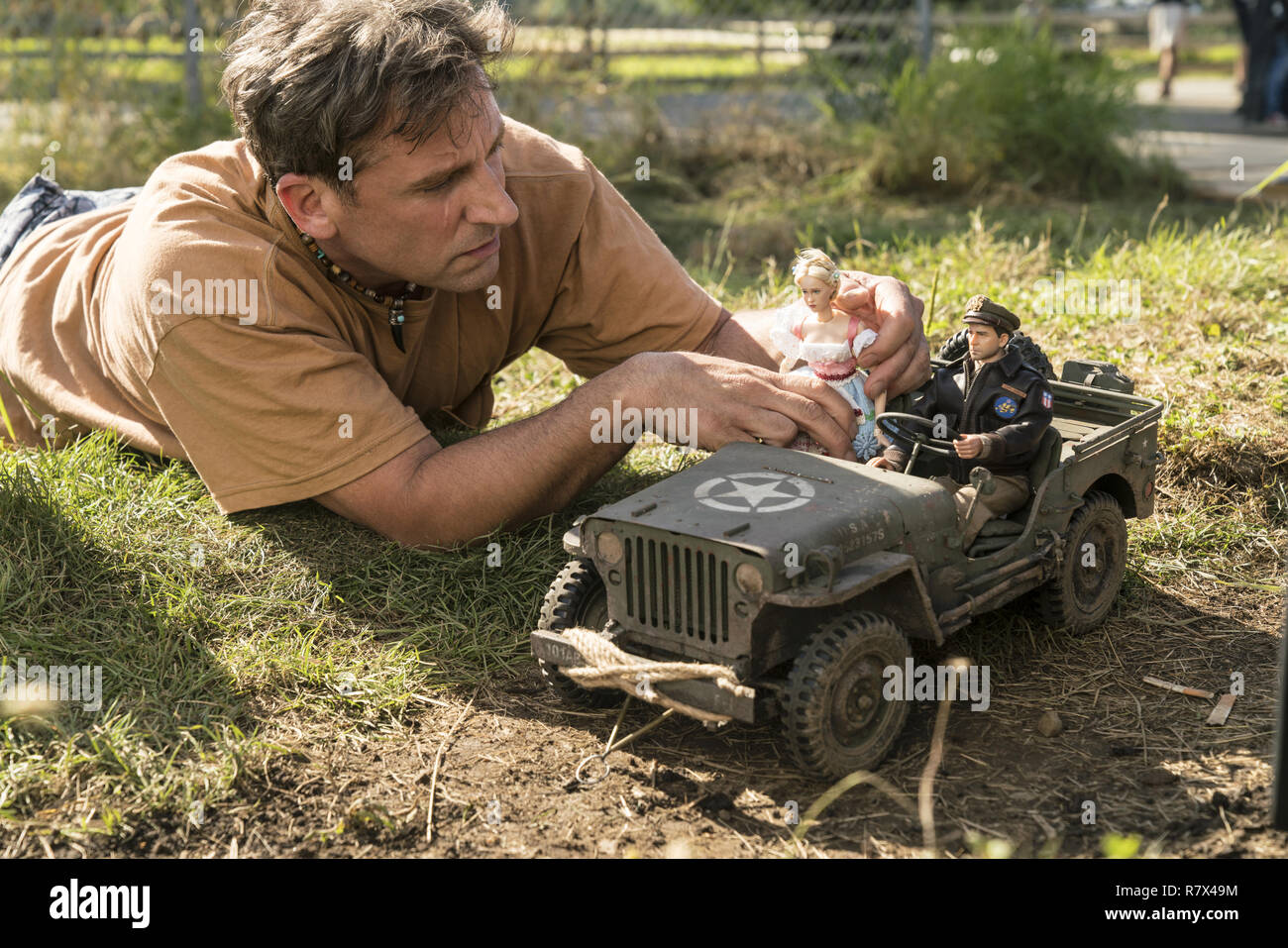 Steve Carell as Mark Hogancamp photographs the dolls for his fictional town in 'Welcome to Marwen,' directed by Robert Zemeckis.  Photo Credit: Universal Pictures and Storyteller Distribution Co., LLC. / The Hollywood Archive - Stock Image