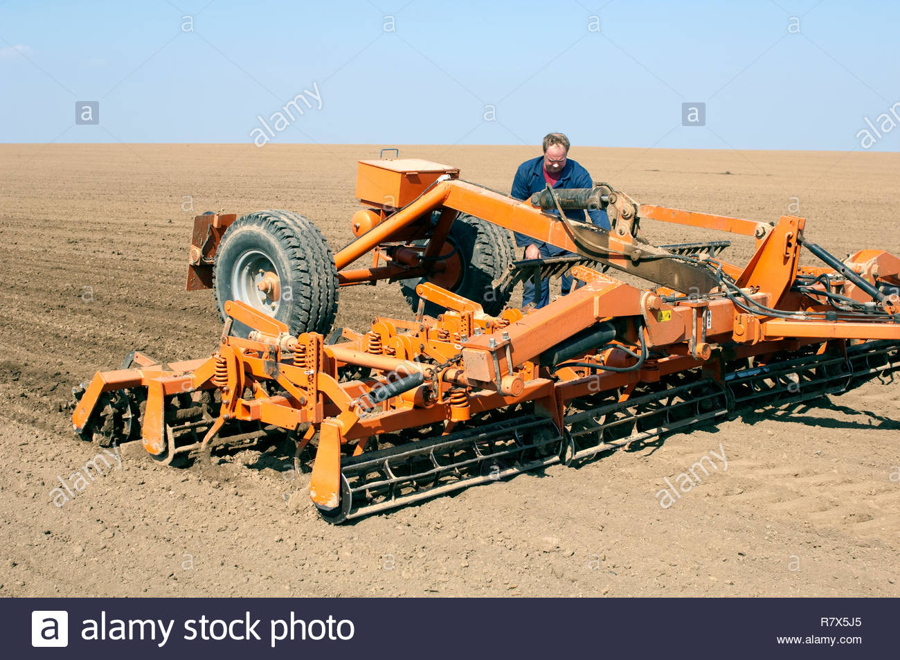 Spring field with cultivator, which is repaired by farmer. Stock Photo