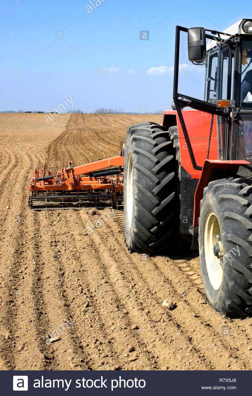 Tractor prepares spring field for seeding. Driver in cabine. Stock Photo