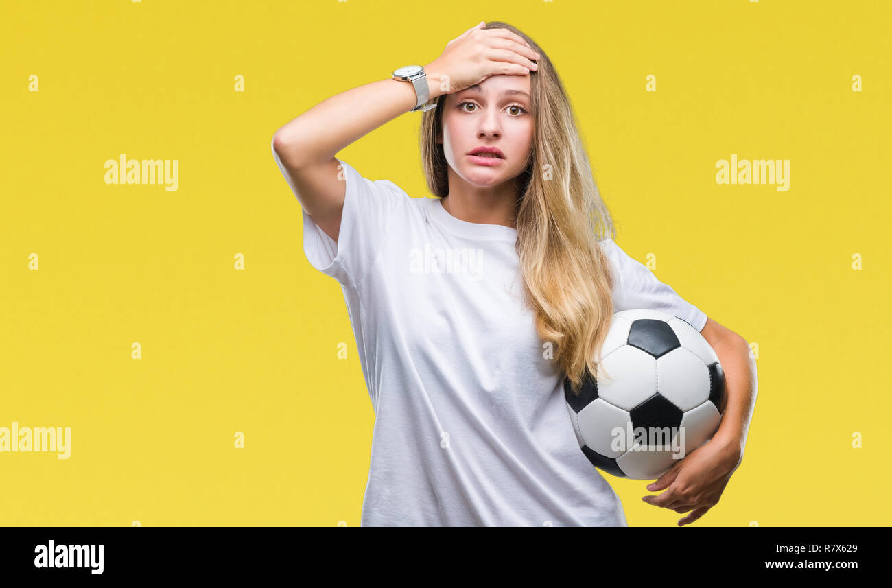 ccbb6da36 Young beautiful blonde woman holding soccer ball over isolated background  stressed with hand on head