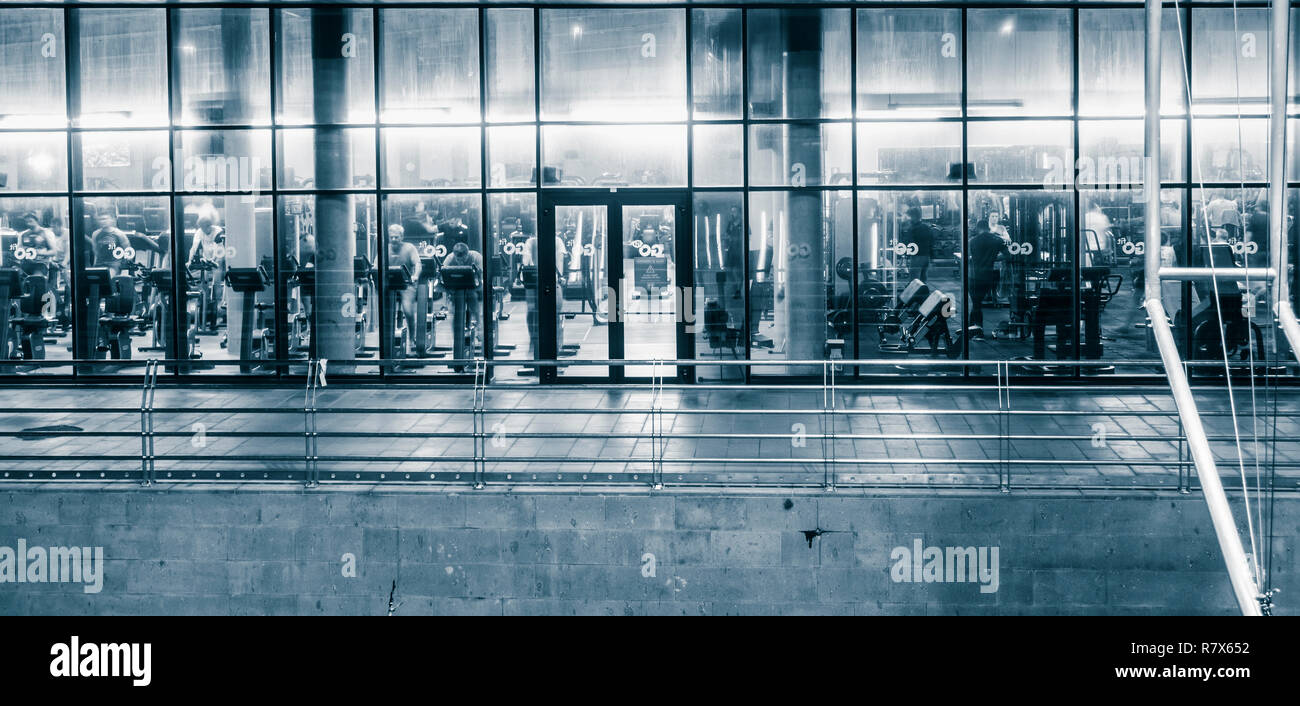 Night time view from street of people using exercise machines in gym. - Stock Image