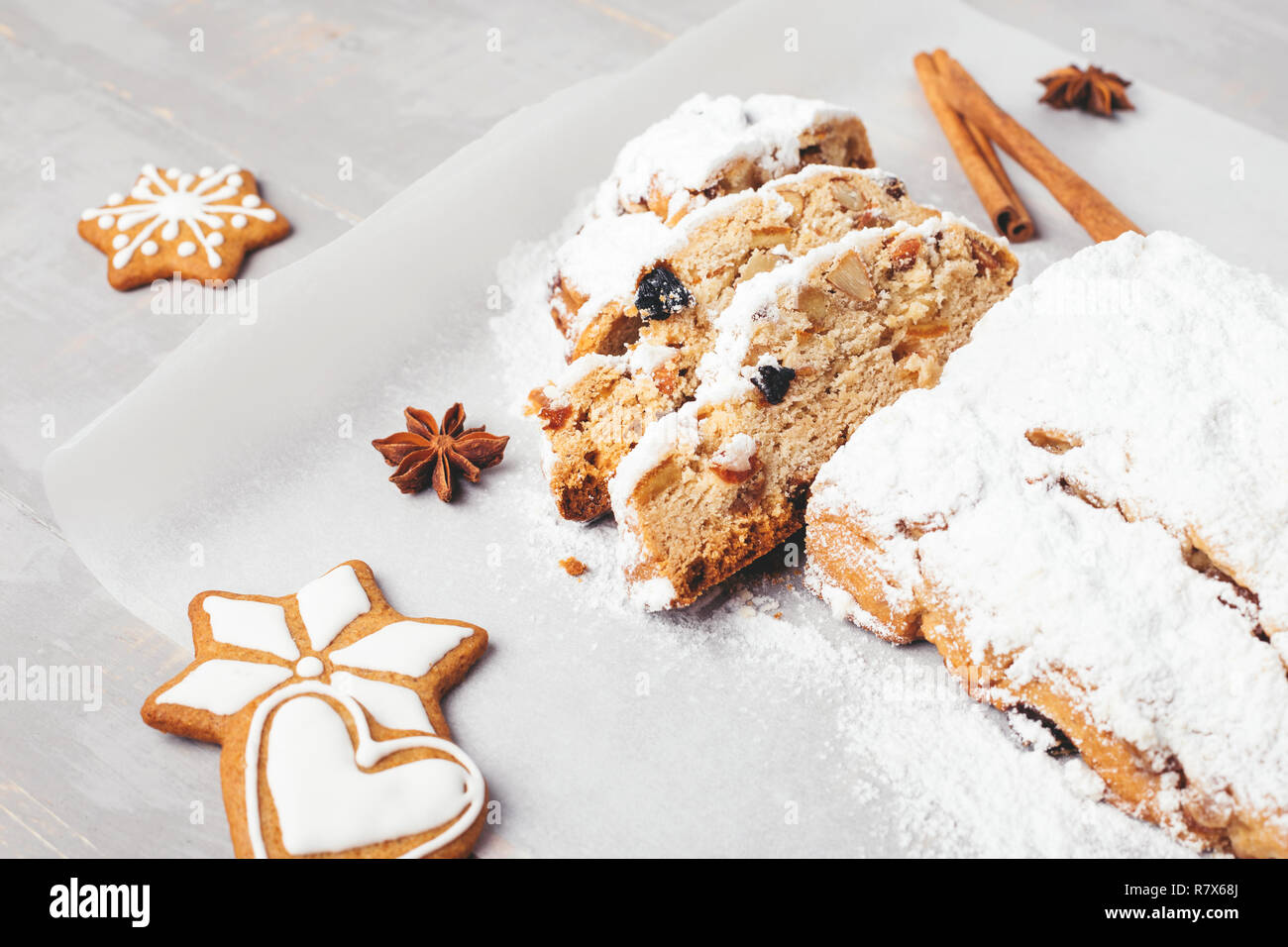 Traditional Christmas stollen with gingerbread, cinnamon, anise stars on grey wooden table. Shot at angle. - Stock Image