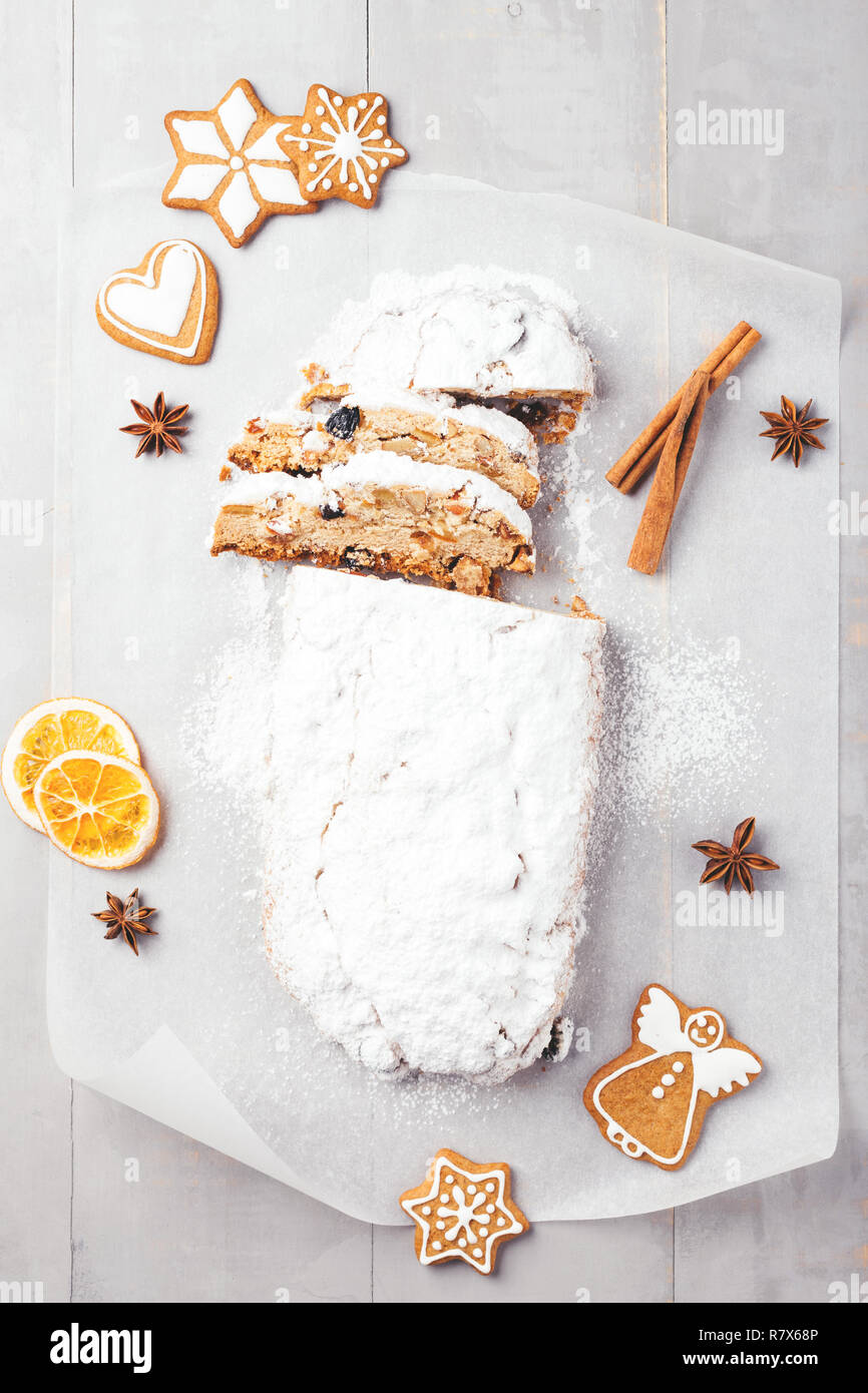 Traditional Christmas stollen with gingerbread, cinnamon, anise stars and orange chips on grey wooden table. Top view. - Stock Image