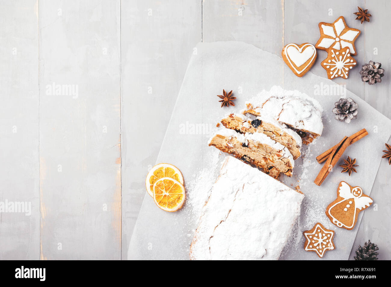Traditional Christmas stollen with gingerbread, cinnamon, anise stars and orange chips on grey wooden table. Top view with copy space. - Stock Image
