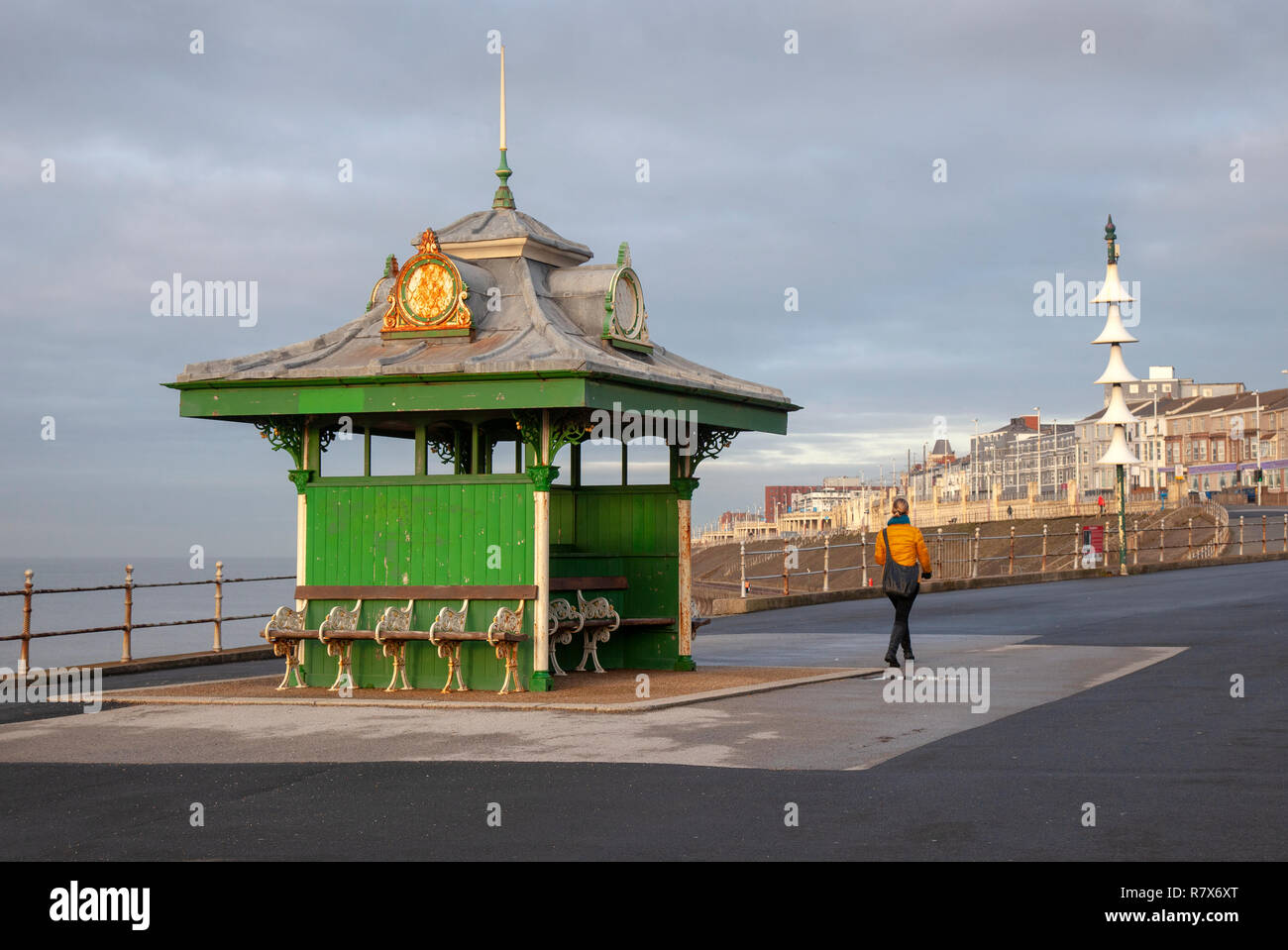 People passing decorated Edwardian seafront promenade Shelters in Blackpool, UK. The British seafront shelter is a public architecture that dates to the mid-19th century. Builders have employed structural cast & wrought iron, archetypal Victorian engineering materials and design with, decoration, curling, organic brackets and columns. - Stock Image