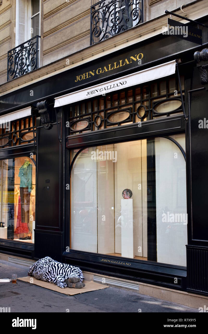 Paris, France A homeless sleeps on cartons in front of a luxurious boutique at the Marais quarter. August 2018, poverty problem in huge cities. - Stock Image