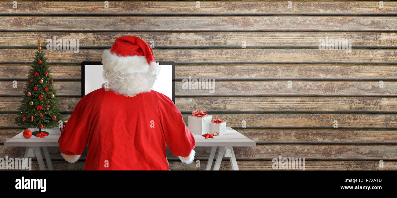Santa Claus send greeting cards online. Copy space beside on wooden wall. - Stock Image
