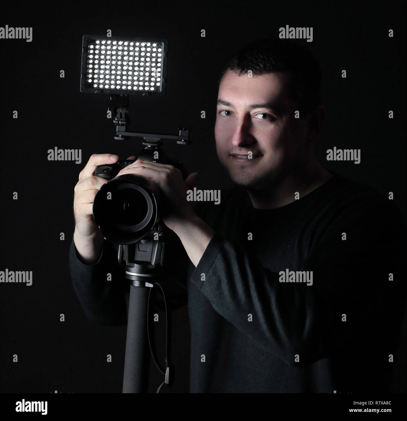 professional photographer with camera on tripod.isolated on black background - Stock Image