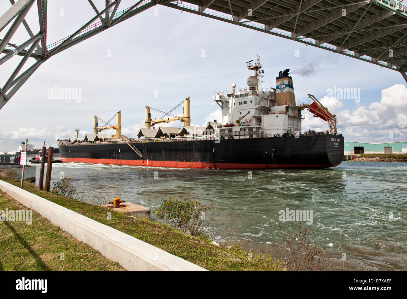 Cargo ship transporting grain, entering Port of Corpus Christi, passing under Harbor bridge. Stock Photo