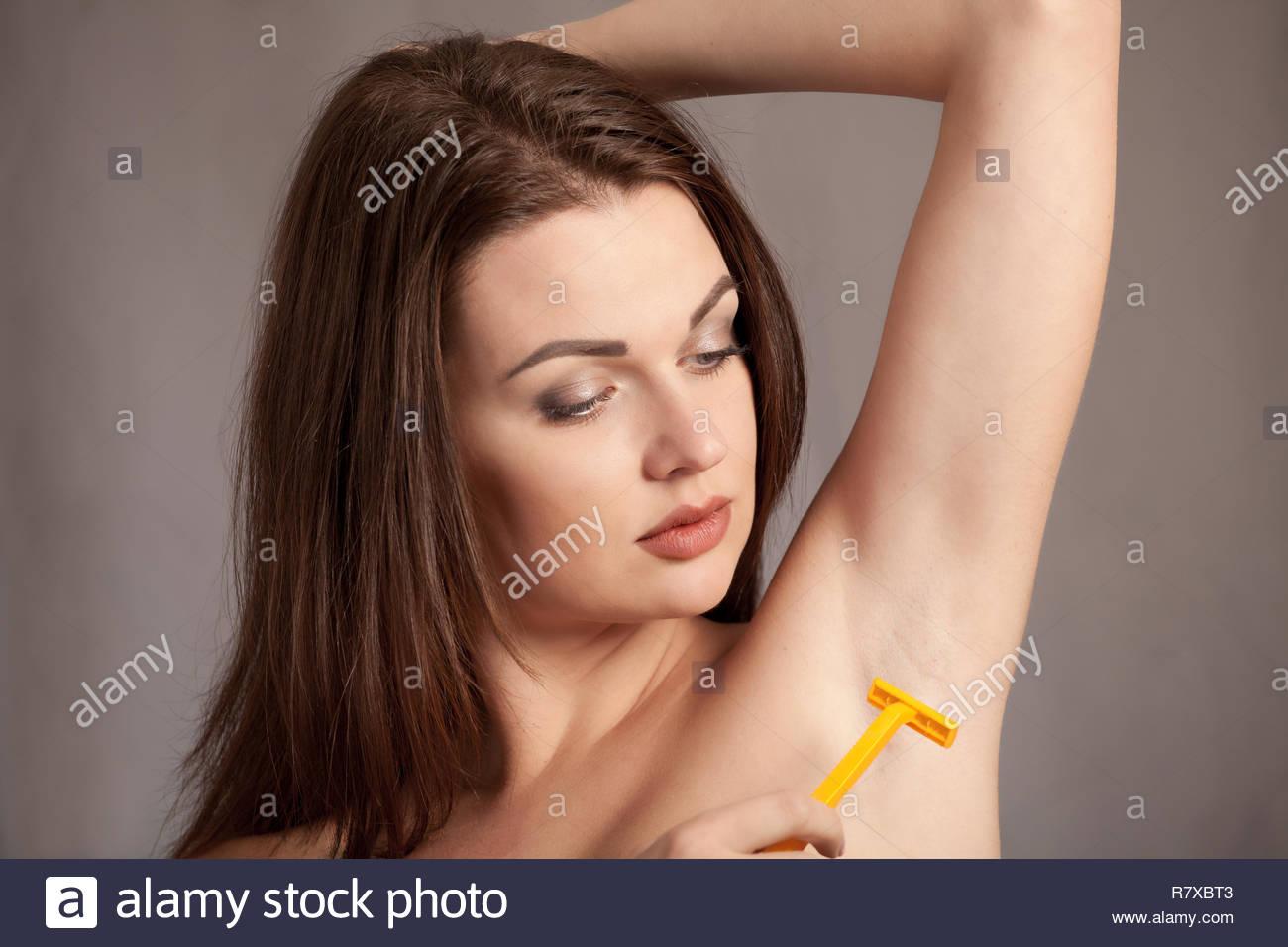 Young woman armpit depilation, epilation, shaving with razor - Stock Image