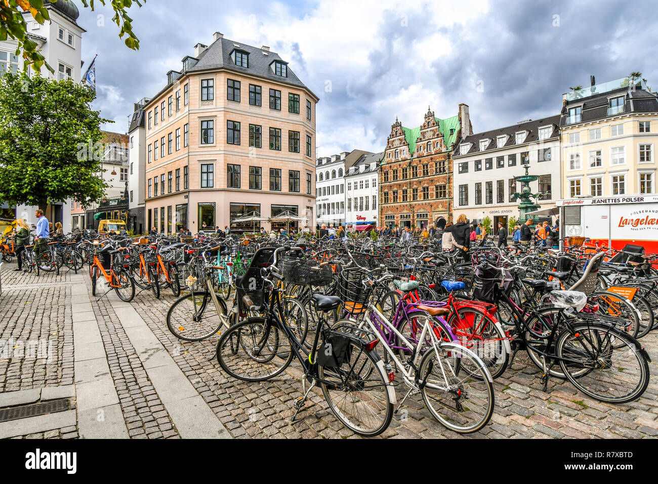 Bicycles parked alongside the Stork Fountain in the Stroget shopping district, the longest pedestrian street in the world, in Copenhagen, Denmark. - Stock Image