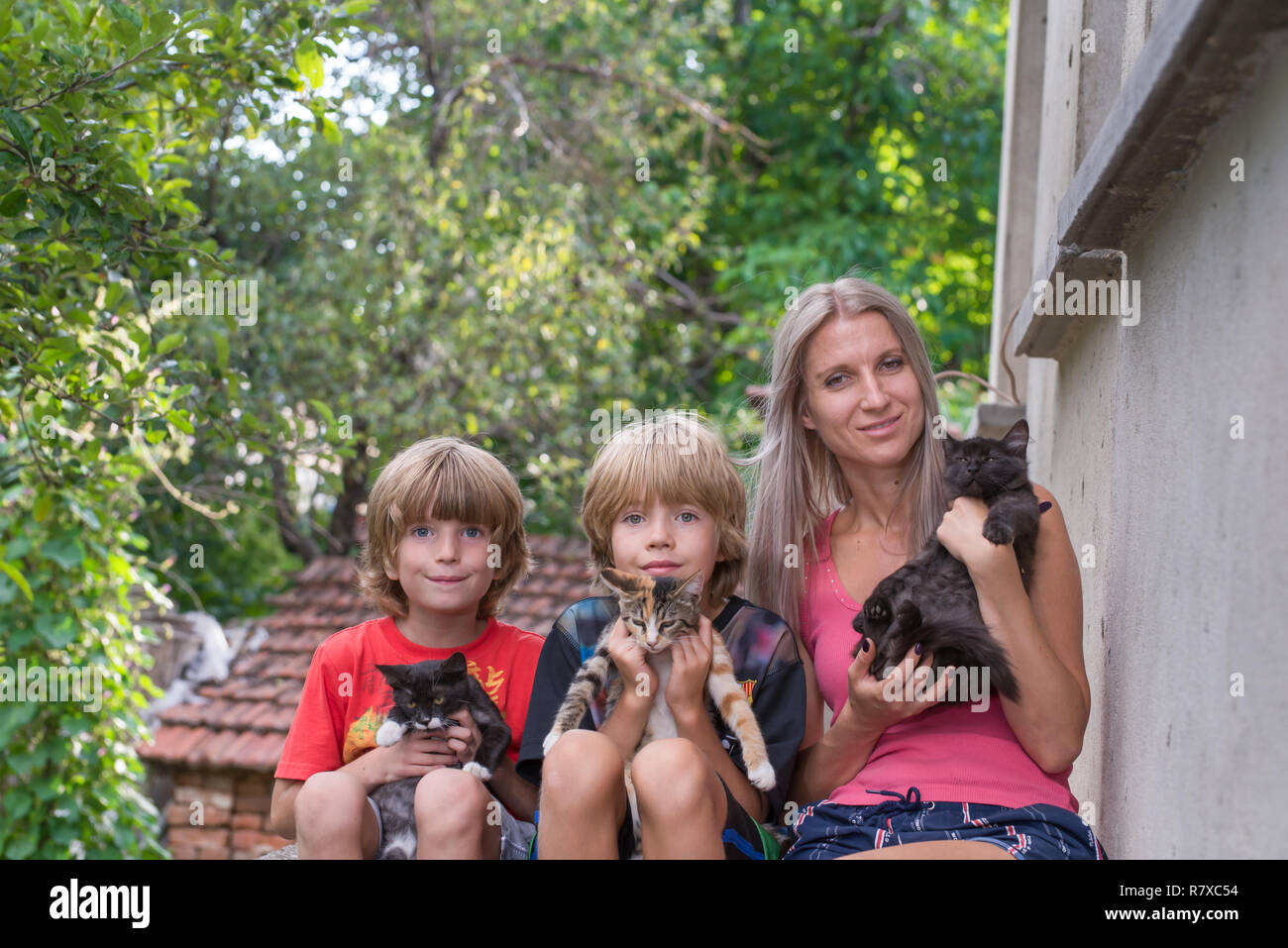 Mother with her two sons, sitting and holding cats - Stock Image