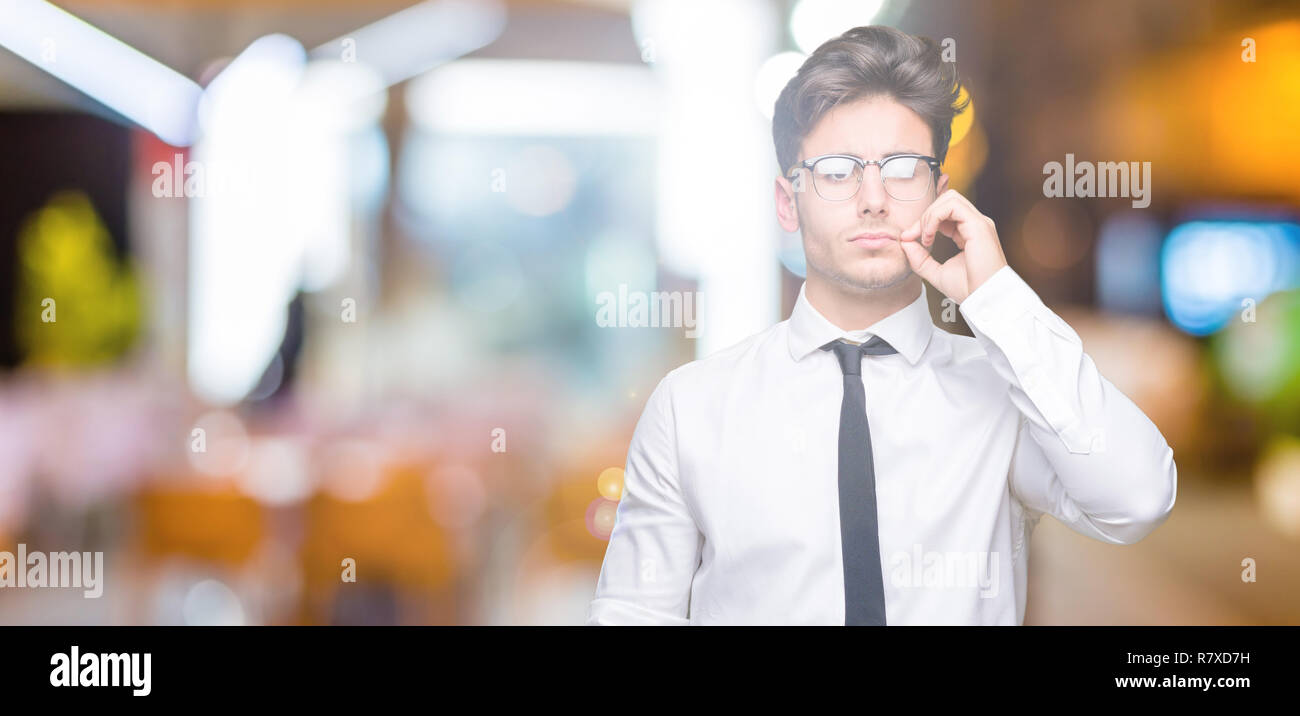 Young business man wearing glasses over isolated background mouth and lips shut as zip with fingers. Secret and silent, taboo talking - Stock Image