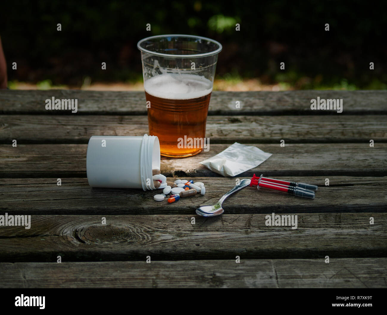 A glass of beer, pills, barbiturates, drugs, cocaine, heroin, a syringe and a spoon on a table. Drug addiction concept - Stock Image