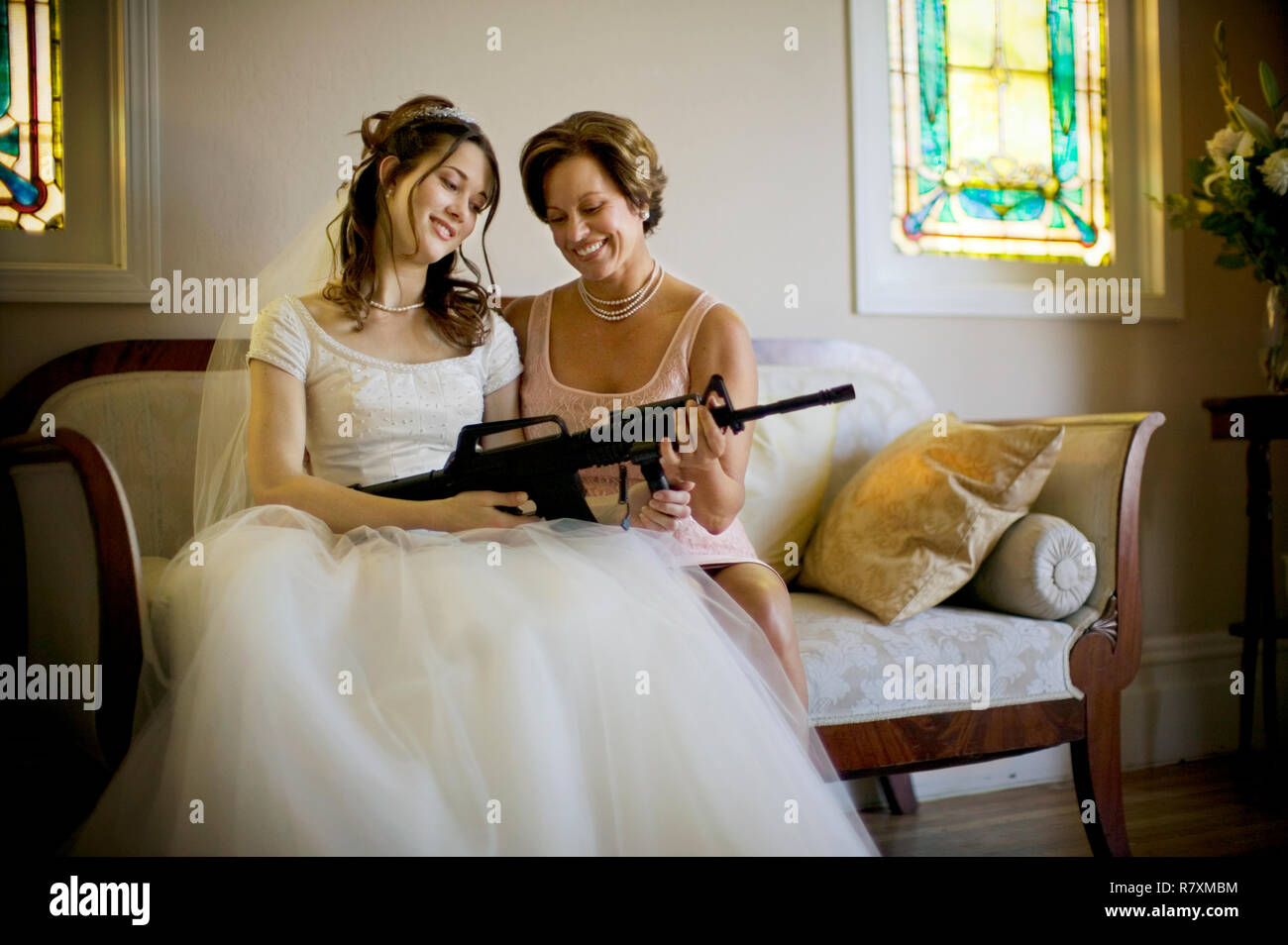Young Bride And Her Mother Smiling While Holding A Machine