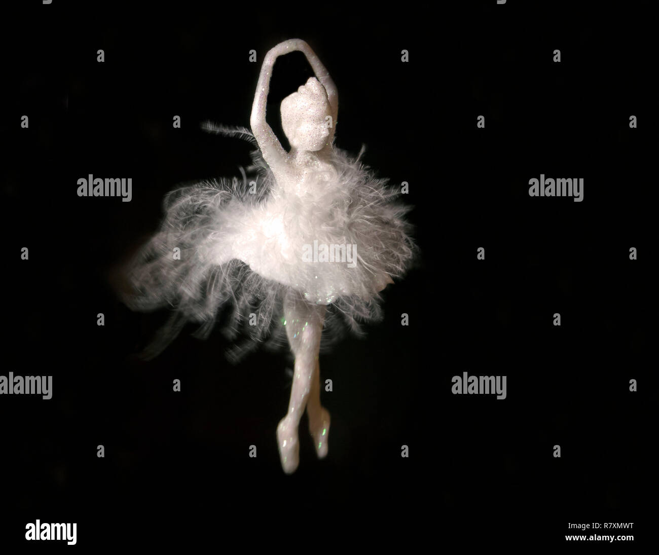 A beautiful white hanging ballerina with feathers against a dark background Stock Photo