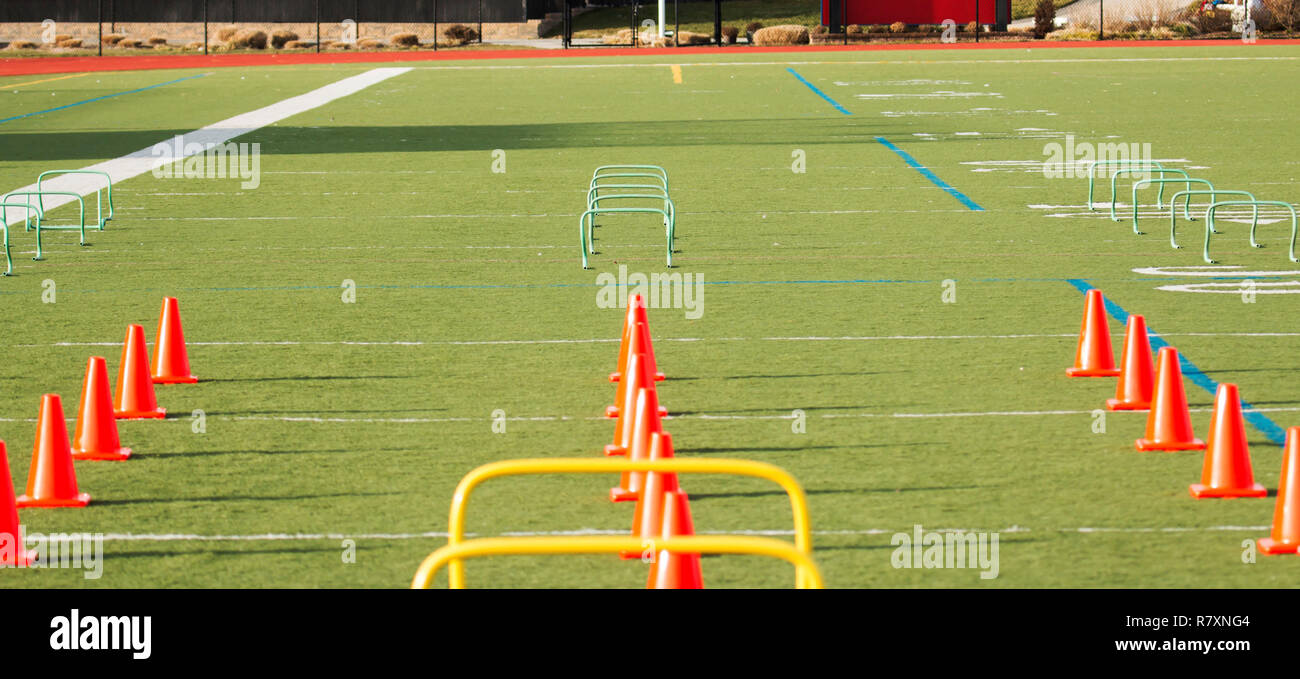 Orange cones and green hurdles are set up for speed and agility training on a turf field - Stock Image