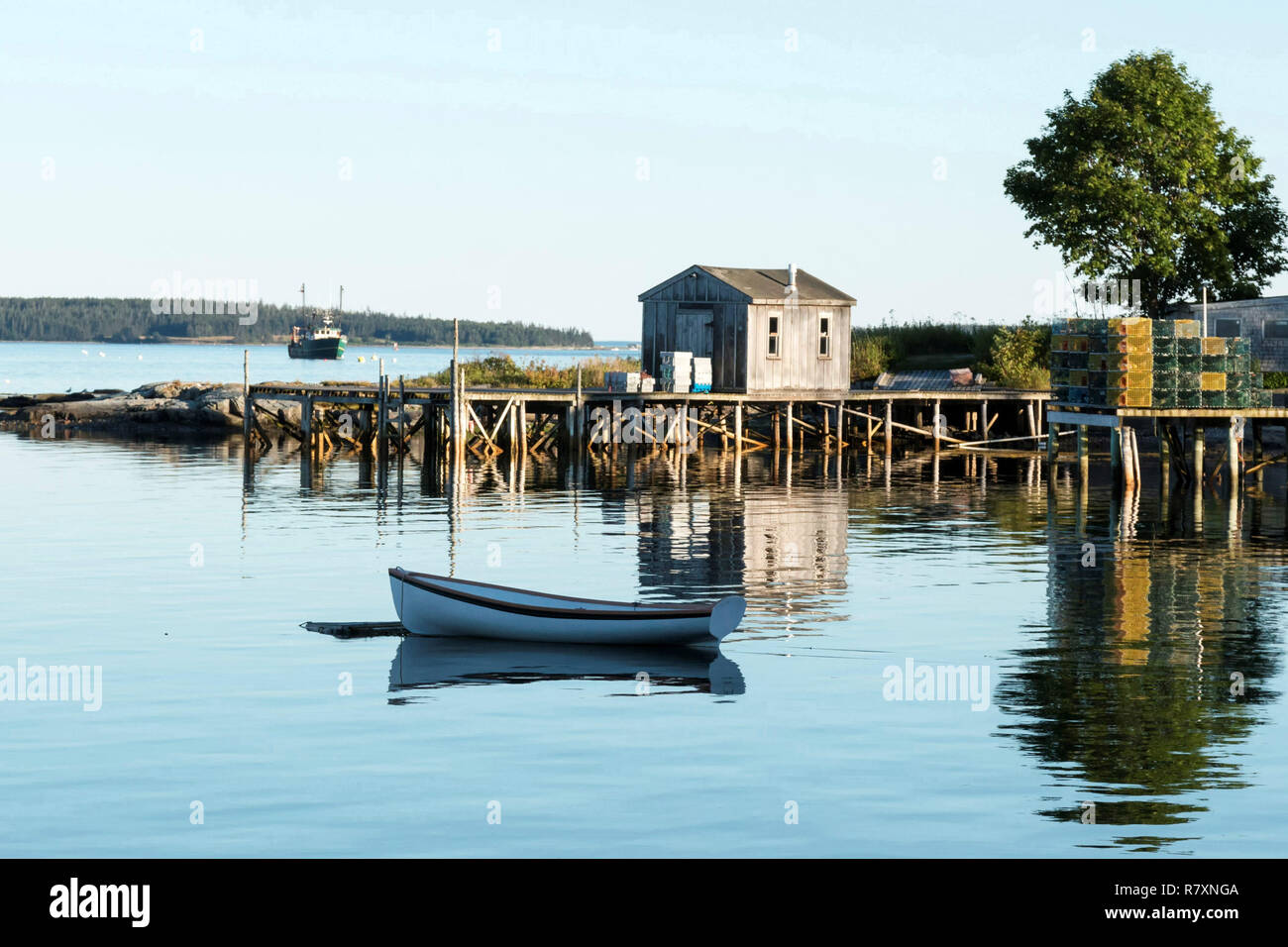 View of Bass Harbor Maine from the deck of Thurston's Lobster pound with a dock, lobster traps, boat house, tree and row boat reflections visible. Stock Photo