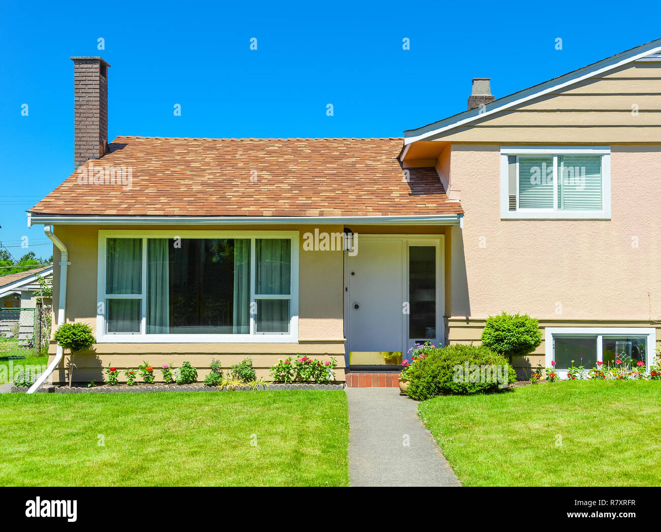 Pathway to the entrance of residential house over mowed lawn on the front yard - Stock Image