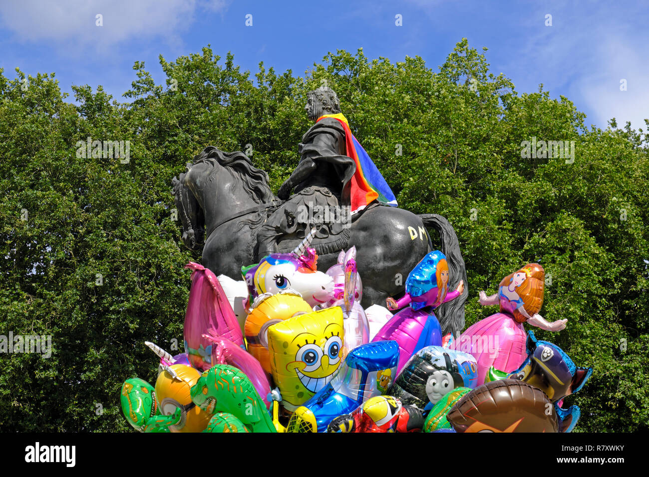 In Bristol, UK a balloon seller walks past a statue of William III which is wearing a Pride flag as a cloak during Bristol Pride 2017. - Stock Image