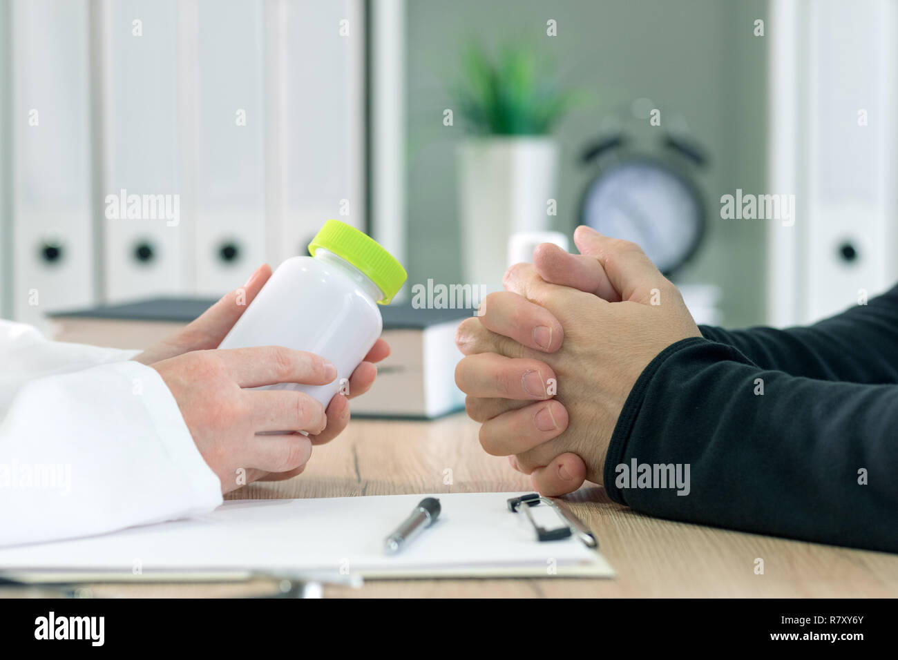 Doctor and patient discuss dietary supplement therapy in medical office during consultation - Stock Image